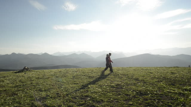 couple look out from grassy ridgecrest, above mountains - 避ける点の映像素材/bロール
