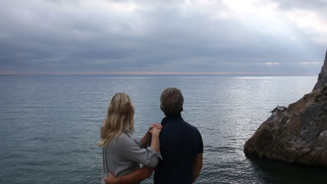 couple look out to sea, from rock promontory - tunic stock videos & royalty-free footage