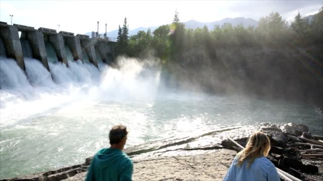 coppia cerca in direzione idroelettrica struttura all'alba - diga video stock e b–roll