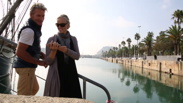 couple look past marina to historic center, takes pic - see other clips from this shoot 56 stock videos & royalty-free footage