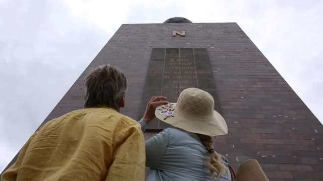 Couple look up towards Monument to the Equator