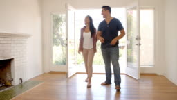 Couple Looking Around New Home On Moving Day