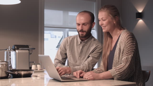 couple looking at a laptop in kitchen - mid adult couple stock videos & royalty-free footage