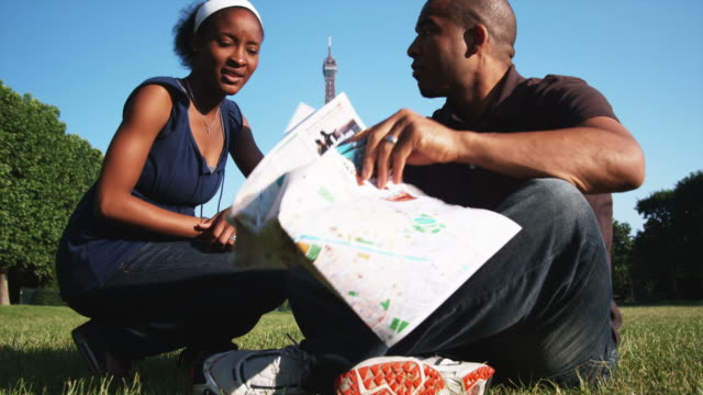couple looking at a map while sitting on the grass in front of the Eiffel tower