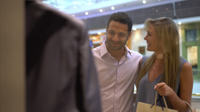 couple looking at a store window and talking about it ready to buy it - window display stock videos & royalty-free footage