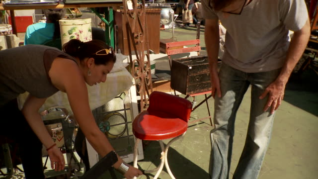ms td tu couple looking at antique stool in flea market, new york city, new york, usa - möbel stock-videos und b-roll-filmmaterial