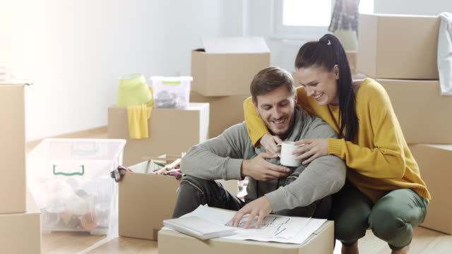 Couple looking at apartment plans, drink coffee and smiling in their new home