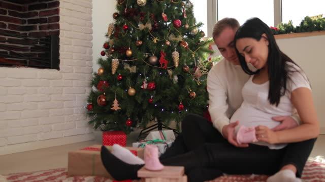 vídeos de stock, filmes e b-roll de casal olhando botinhas de bebé - cuidado pré natal