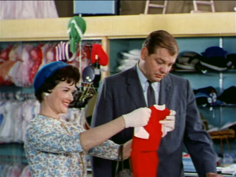 1962 couple looking at baby clothing in department store / woman holds outfit up to embarrassed man - 1962年点の映像素材/bロール