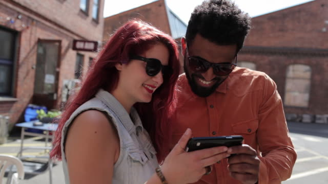 Couple looking at cell phone together in sunshine, smiling, typing