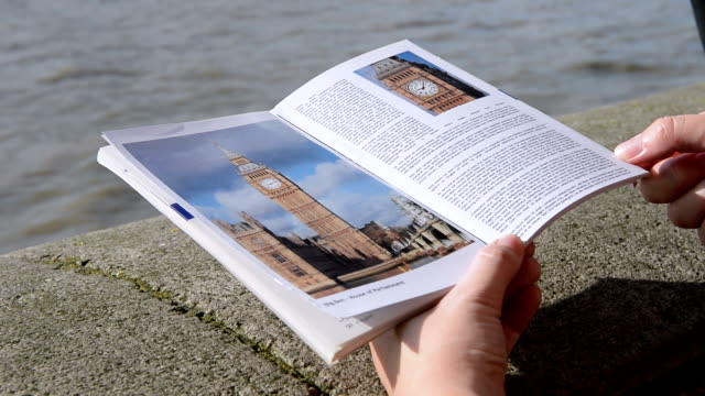 Couple looking at city guide, pointing to Big Ben, London