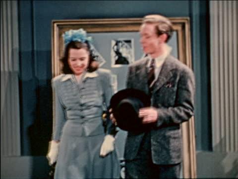 1941 couple looking at coming attractions board at cinema / industrial - biosalong bildbanksvideor och videomaterial från bakom kulisserna