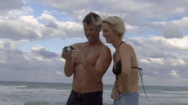 CU ZO ZI Couple looking at digital camera and laughing on beach / Miami, Florida, USA