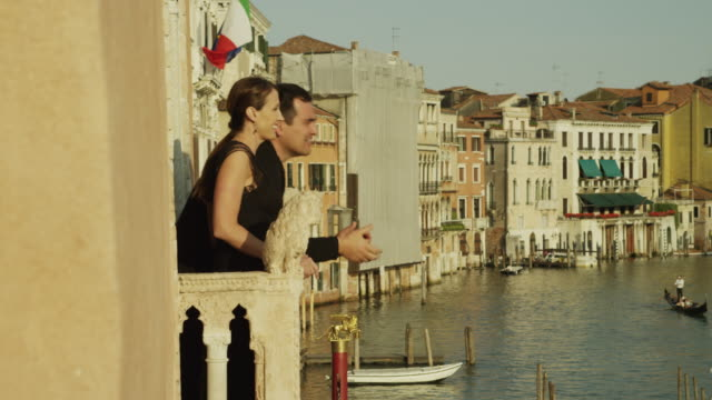 WS Couple looking at Grand Canal from balcony / Venice,Veneto