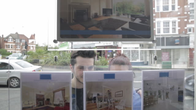 cs couple looking at houses for sale at estate agent's window - windows stock videos and b-roll footage