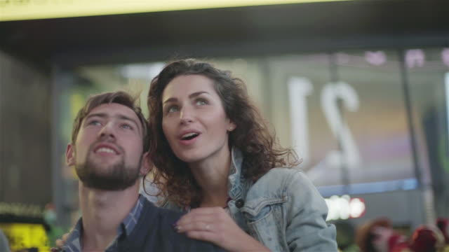 vidéos et rushes de couple looking at illuminated billboards in times square new york city new york - billboard