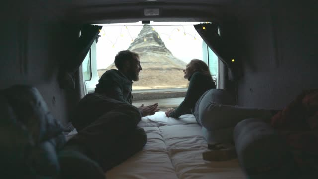 couple looking at kirkjufell mountain in iceland from camper van - island stock videos and b-roll footage