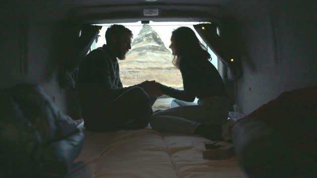 Couple looking at Kirkjufell mountain in Iceland from camper van