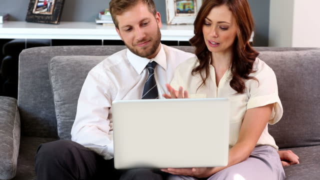 couple looking at laptop together - mid adult couple stock videos & royalty-free footage