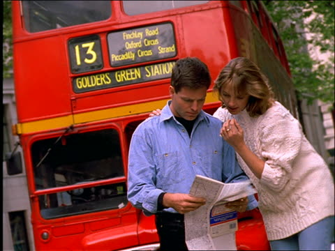 Couple looking at map and pointing / double decker bus in background / London