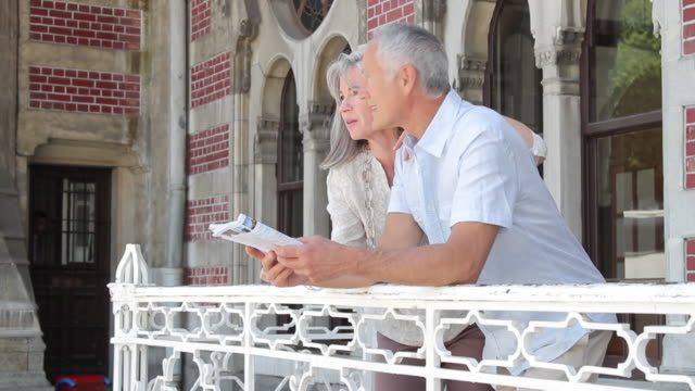 stockvideo's en b-roll-footage met couple looking at map, cityscape in background, istanbul, turkey - jong van hart