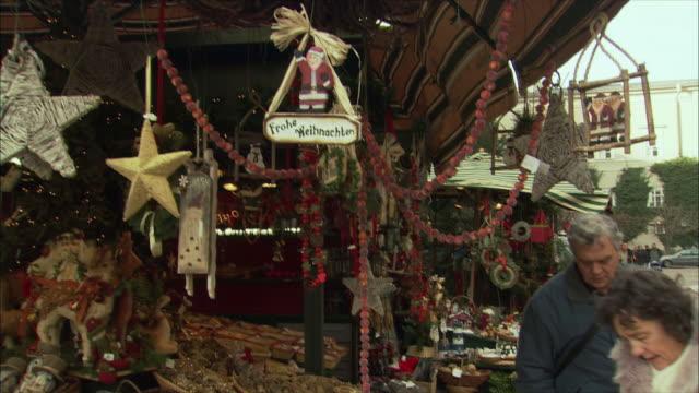 stockvideo's en b-roll-footage met ms pan couple looking at merchandise at christmas market stall / salzburg, austria - oostenrijkse cultuur