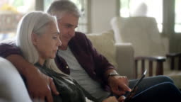 Couple looking at photographs in digital tablet