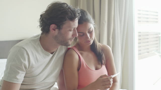 couple looking at pregnancy test - pregnant stock-videos und b-roll-filmmaterial