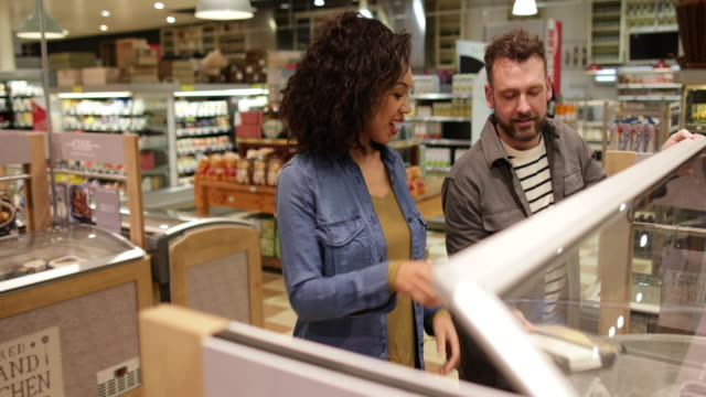 Couple looking at ready meal in grocery store
