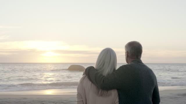 vidéos et rushes de couples regardant la mer du rivage pendant le coucher du soleil - quinquagénaire