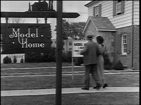 b/w 1935 couple looking at sign in front of model home / educational - 1935 stock videos & royalty-free footage