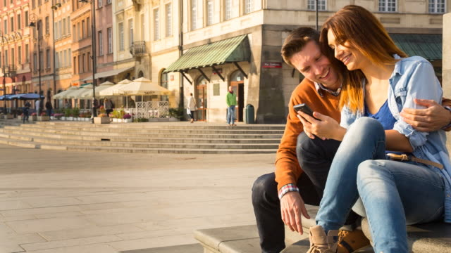 ms couple looking at smartphone content outdoors - warsaw stock videos & royalty-free footage