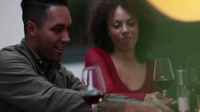 couple looking at smartphone together at a meal - date night romance stock videos and b-roll footage