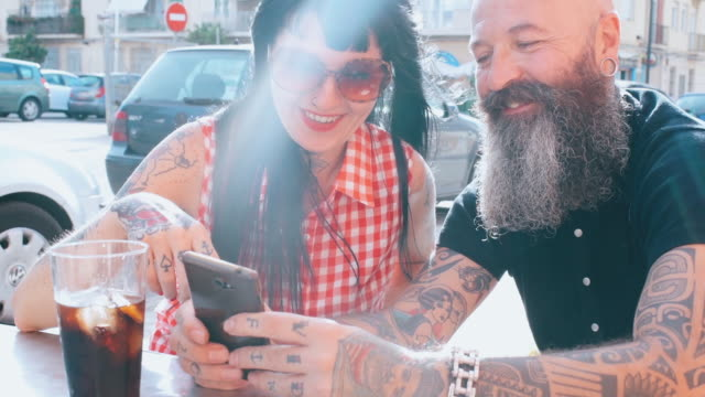 vídeos y material grabado en eventos de stock de couple looking at smartphone - coca cola