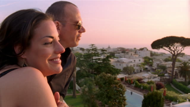 Couple looking at sunset from cliff overlooking town / Capri