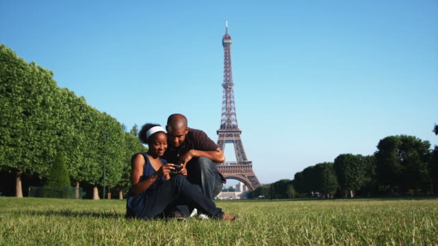 couple looking at their photos in front of the Eiffel tower