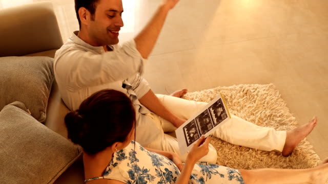 MS Couple looking at ultrasound pictures in living room / India
