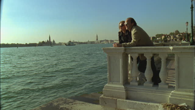 WS Couple looking at view of canal with waterfront in background / Venice, Italy
