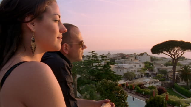 Couple looking at view of town at sunset / Capri