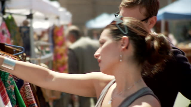 slo mo cu couple looking at vintage costumes in flea market, woman trying one on, new york city, new york, usa - mercato delle pulci video stock e b–roll