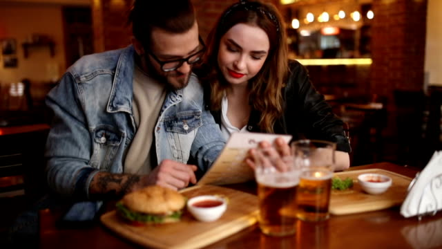 couple looking in a menu at the pub - ristorante video stock e b–roll