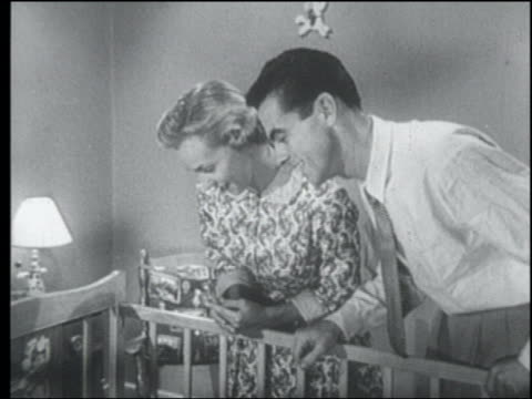 b/w 1955 couple looking into crib + talking babytalk - 1955 stock videos & royalty-free footage