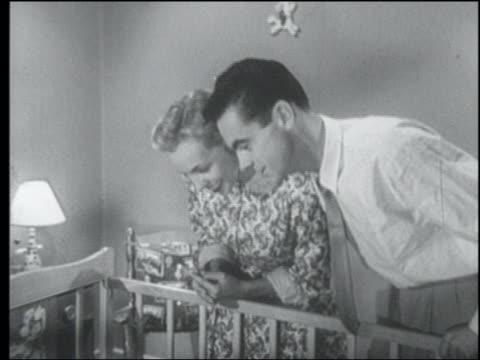 B/W 1955 couple looking into crib + talking babytalk