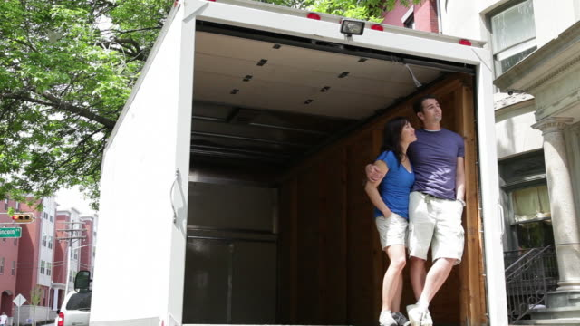 vidéos et rushes de ms pan couple looking  out from empty moving truck / newark, new jersey, united states - véhicule utilitaire léger