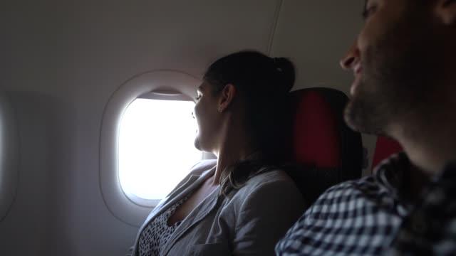 paar schaut durch flugzeugfenster - passenger stock-videos und b-roll-filmmaterial
