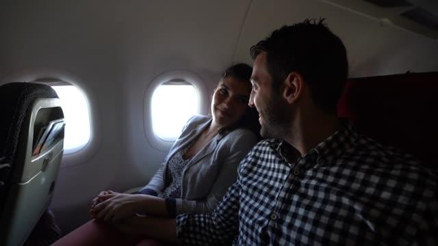 vídeos y material grabado en eventos de stock de pareja mirando a través de la ventana del avión - pareja joven