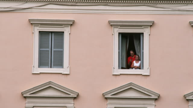 ws couple looking through window / rome, italy - facade stock videos & royalty-free footage