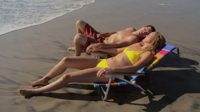 vídeos y material grabado en eventos de stock de couple lounges on beach chairs at waters edge at the beach - bañador de natación