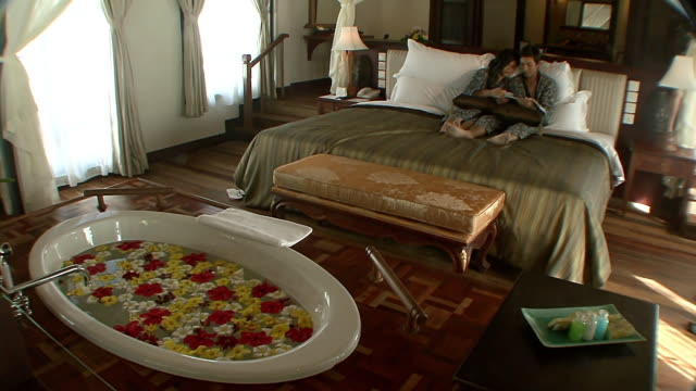 ms couple lounging on bed in luxury hotel room / sihanoukville, cambodia - adagiarsi video stock e b–roll