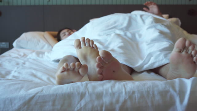 couple lovers feet relaxation on the comfortable bed. - barefoot stock videos & royalty-free footage